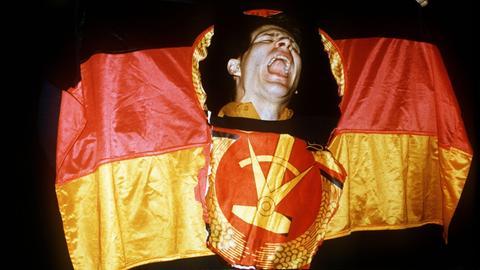 Ein Mann schaut durch das herausgeschnittene Emblem der DDR-Fahne.