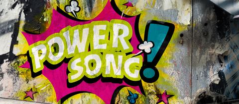 """Knalliges Graffiti auf Mauer mit Text """"hr1-Powersong"""""""