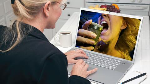Eine Frau schaut ein Konzert am Computer.