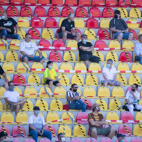 Fußballfans im Stadion unter Einhaltung von Abstandregeln