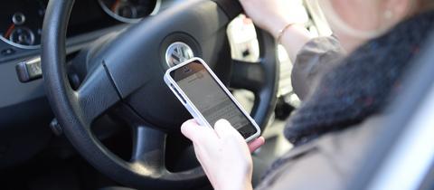Frau schaut im Auto auf ihr Handy, während sie fährt