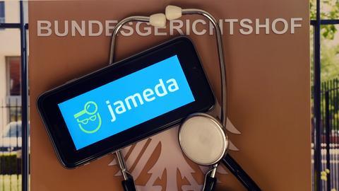 Handy mit Jameda-Logo vor einem Schild des Bundesgerichtshofs
