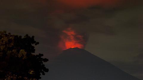 Eine rot erleuchtete Rauchsäule steigt aus dem Vulkan Agung auf