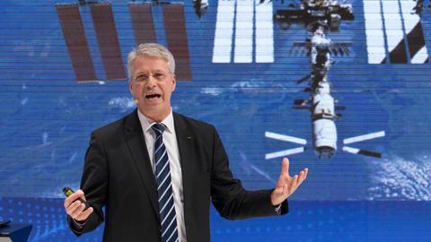 Thomas Reiter vor dem Bild eines Satelliten