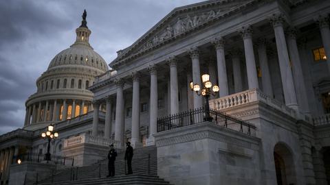 Das Capitol steht in Washingtonunter einem dunklen, wolkigen Himmel da.