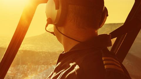 Pilot im Hubschrauber fliegt in den Sonnenaufgang