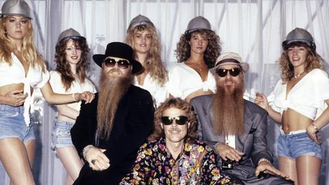 Die drei ZZ Top-Mitglieder mit Sonnenbrillen, umgeben von jungen Frauen