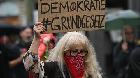 """Eine Frau hält während eines Protestzuges durch die Frankfurter Innenstadt ein Plakat mit der Aufschrift """"Freiheit Demokratie #Grundgesetz"""" hoch"""