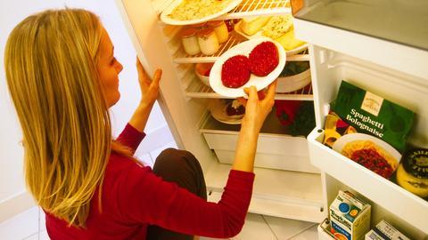 Ein Frau schaut in den Kühlschrank.