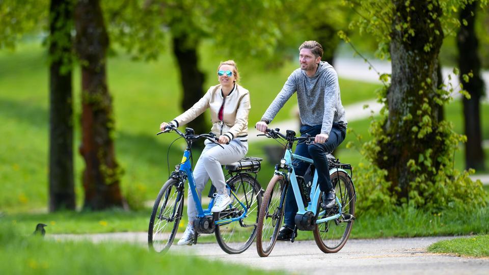 Ein Paar fährt mit Pedelecs durch die Natur.