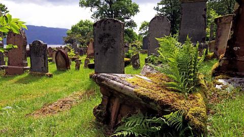 Ein alter Friedhof mit umgestürzten Grabsteinen.