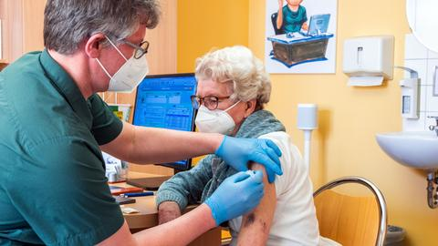 Hausarzt impft Patientin