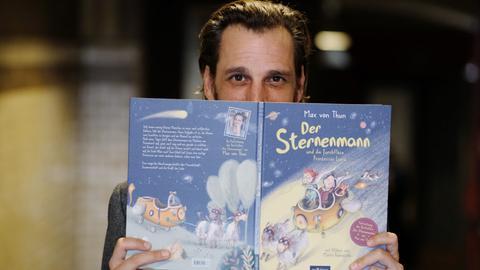 """Max von Thun zeigt sein Kinderbuch """"Der Sternenmann und das große Abenteuer""""."""