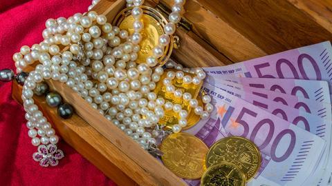 Gold in Münzen und Barren mit Schmuck auf rotem Samt.