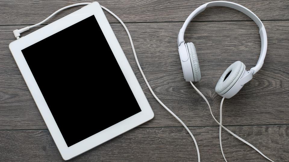Tablet-Computer mit angeschlossenen Kopfhörern auf einem Tisch
