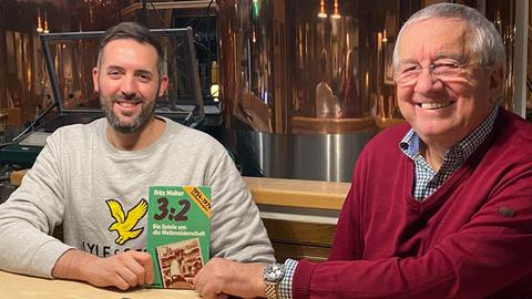 Werner Reinke und Philipp Hofmeister halten Fritz Walters Buch in die Kamera.