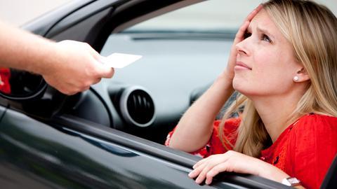 Eine Frau schaut verzweifelt aus ihrem Auto raus, weil ihr ein Bußgeldbescheid durchs Fenster gereicht wird.