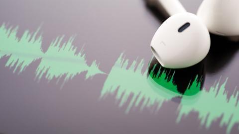 Weiße Stöpselkopfhörer vor Audiofrequenzkurve