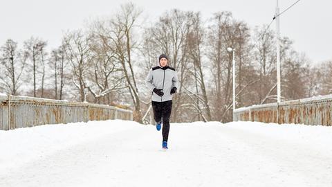 Mann joggt im Schnee